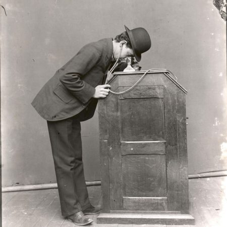 Hombre mirando un kinetoscopio equipado con-sonido sincronizado ©U.S.-Dept. of the Interior,-National Park Service,-Thomas Edison