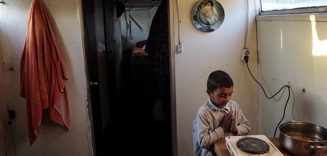 Marus, de 7 años, se calienta las manos junto a una estufa portátil antes de ir a la escuela el día del desalojo de su remolque en Las Tablas, norte de Madrid, el 21 de marzo de 2011. Dos familias gitanas rumanas de cuatro adultos y diez niños vivían en el remolque desde 2008, pero fueron desalojados el lunes por orden de la junta de urbanismo de Madrid. Su casa fue derribado mientras los niños mayores estaban en la escuela. REUTERS/Susana Vera